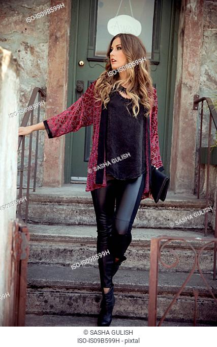 Stylish young woman moving down front door stairs