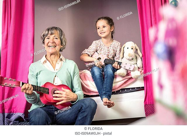 Girl and grandmother playing toy guitars in bedroom