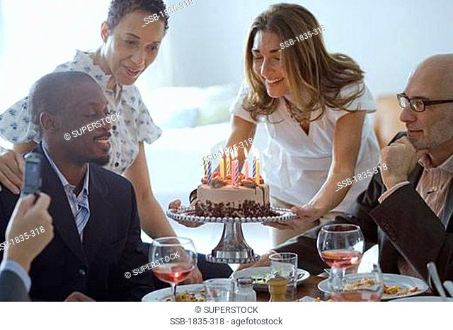 Close-up of a person's hand taking a picture of four people at a party
