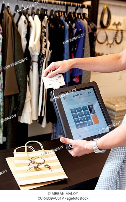 Mature woman using digital tablet to charge customer credit card in fashion boutique