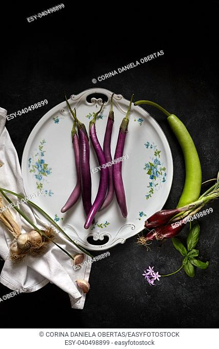 Plate with sicilian agricultural products: eggplant Perlina variety, garlic, spring red onions and a particular squash called cucuzza or zucchetta serpent