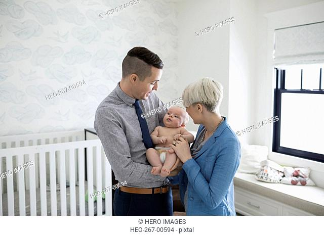 Parents holding baby son in nursery