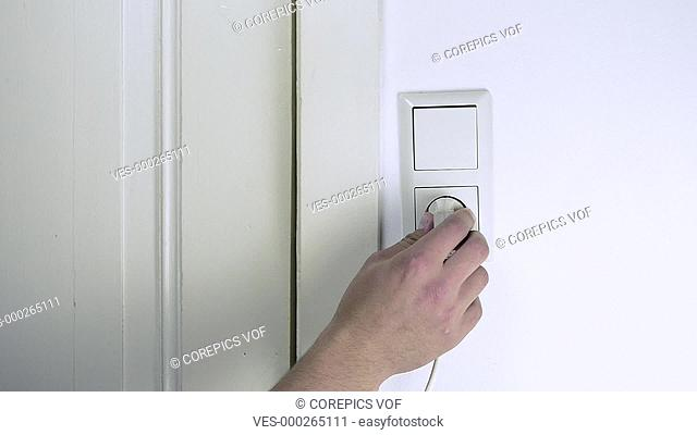 Hand, putting a white plug into a wall socket, and pulling it out again. Conceptual loop about electricity, energy and conservation, preservation