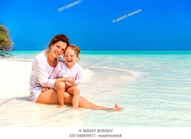 Mother and little daughter playing on sunny beach on Maldives