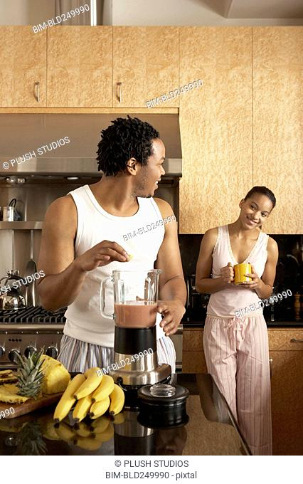 Woman watching man making smoothie in domestic kitchen
