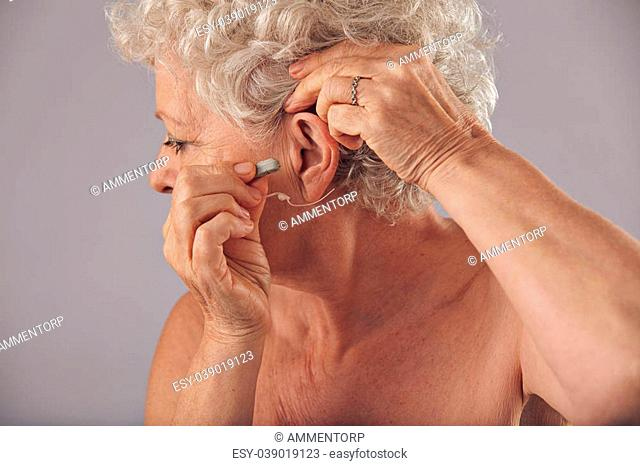 Closeup of a mature woman inserting a hearing aid in her ear. Focus on the hearing aid. Old woman wearing a hearing aid on grey background