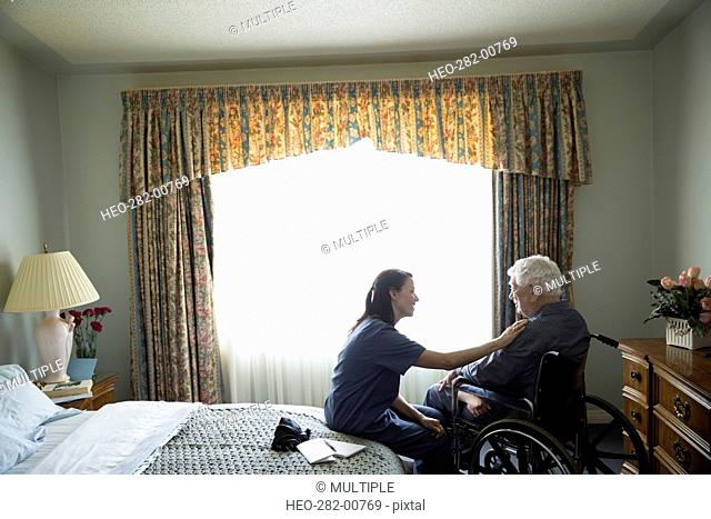 Home caregiver comforting senior man in wheelchair