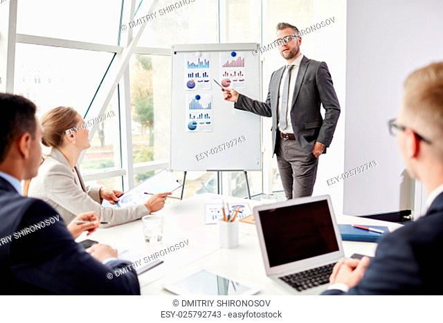 Experienced businessman by whiteboard looking at camera while presenting his review of financial analysis