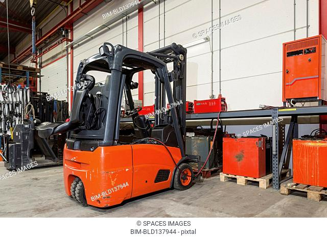 Forklift machinery and shelves in warehouse