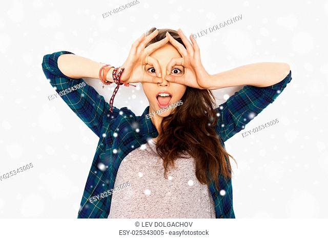 winter, christmas, people and teens concept - happy smiling pretty teenage girl making face and having fun over gray background and snow