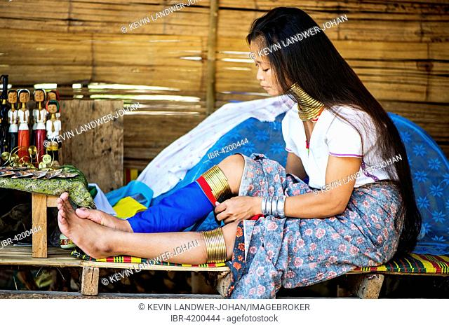 Kayan woman ties fabric on her traditional brass leg rings, Chiang Mai, Thailand