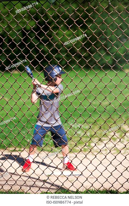 View through chicken wire fence of boy playing baseball