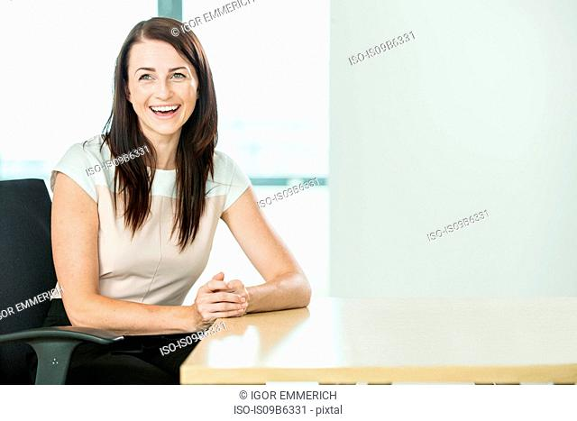 Portrait of businesswoman sitting at desk, laughing