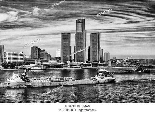 Large bulk carrier cargo ships travel along the Detroit River with the skyline of downtown Detroit, Michigan, USA in the background