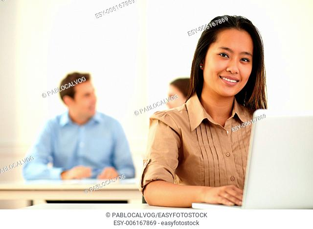 Portrait of lovely young woman smiling at you while working on her laptop and sitting in front of coworker group on workplace