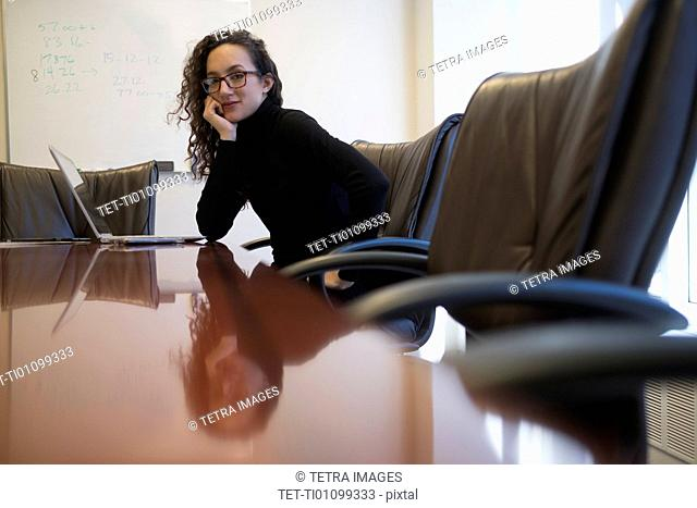 Portrait of young business woman sitting in conference room with laptop