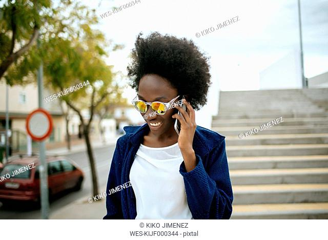 Portrait of young woman wearing mirrored sunglasses talking on mobile phone