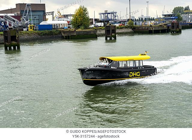 Rotterdam, Netherlands. DHG Water taxi speeding on the Nieuwe Maas River, steaming through Port of Rotterdam Harbor, to transport it's customers and passengers...