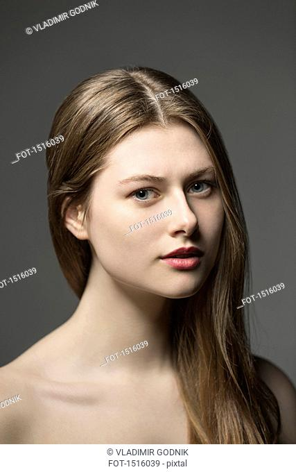 Portrait of beautiful woman against gray background
