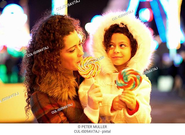 Mother and daughter enjoying lollipop
