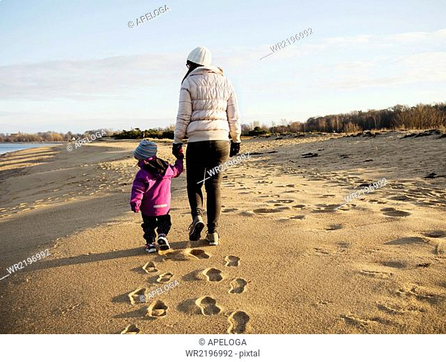 Rear view of mother with daughter walking at beach