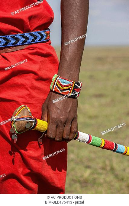 Black man with traditional bracelet and cane
