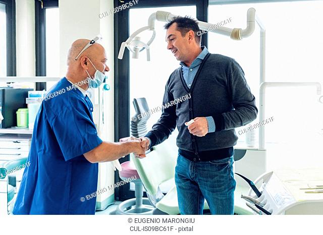 Dentist and male patient in dentist office, shaking hands
