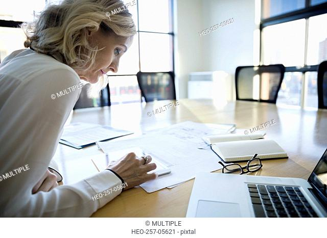 Architect using digital tablet in conference room