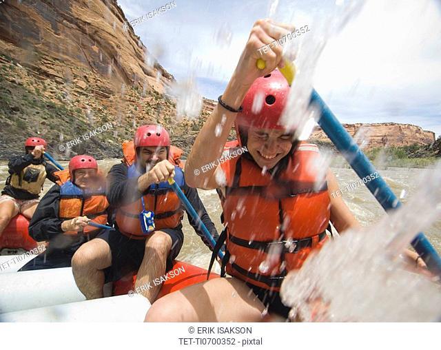 Group of people paddling in raft
