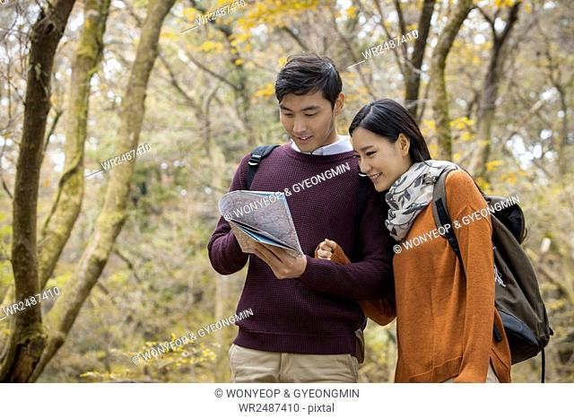 Young smiling couple trekkers arm in arm reading a map in forest in fall