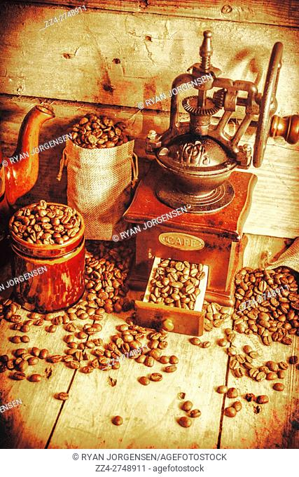 Still life of roasted coffee beans scattered on wooden table. Vintage coffee grinder full of beans. Toned