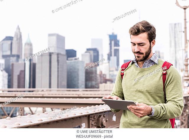 USA, New York City, man on Brooklyn Bridge using tablet