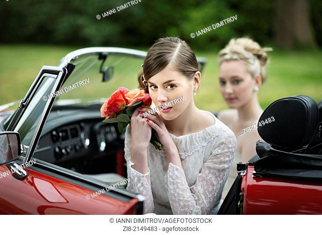 Bride with bouquet of roses in red convertable car