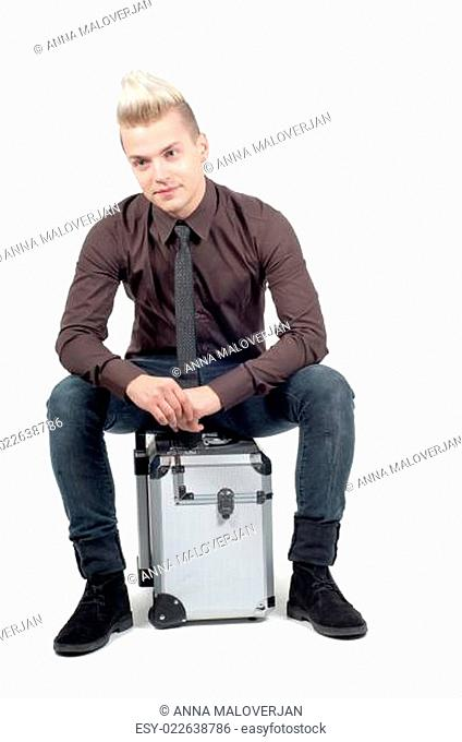 Handsome man sitting on the suitcase