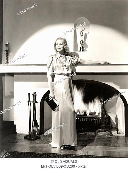 Woman in silk gown standing in front of fireplace