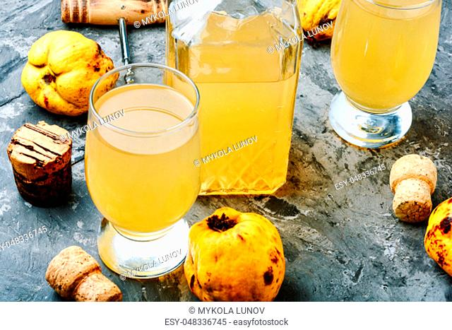 Wine from the fruit of autumn quince.Wine glasses and bottle on stone background
