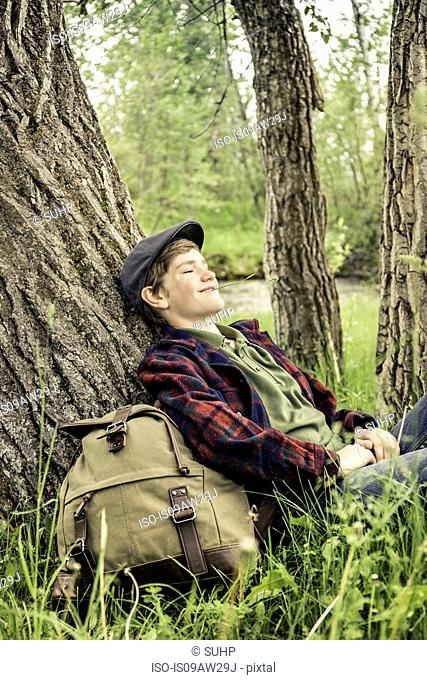 Teen boy wearing flat sitting leaning against tree, eyes closed chewing grass smiling