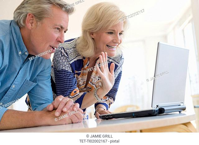 Portrait of couple looking at laptop screen