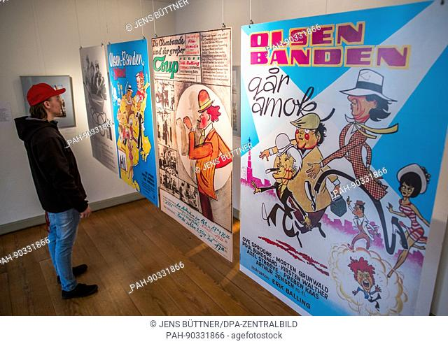 A visitor looks at historical movie posters at a special exhibition on the movie history of the Olsen Gang in Schwerin, Germany, 2 May 2017