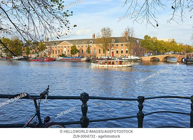 View across the Amstel river towards the Hermitage museum, Amsterdam, Netherlands,. Located in the classical Amstelhof building from 1681