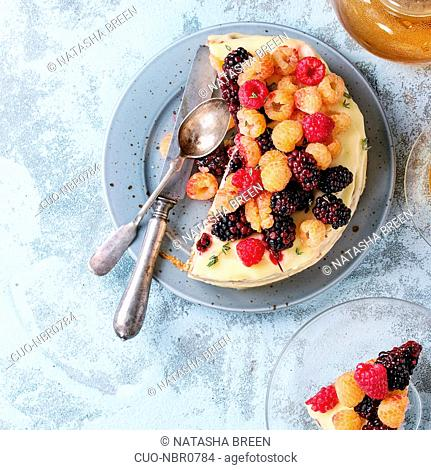 Semi naked cake and piece of cake with lemon cream, decorated by fresh colorful yellow red raspberries and dewberries, served with cup of tea over blue...