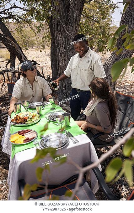 Couple enjoying picnic lunch at Huab Under Canvas, Damaraland, Namibia, Africa