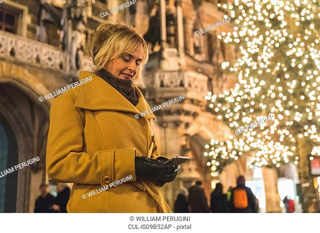 Woman looking at smartphone by christmas tree lights at night, Munich, Germany