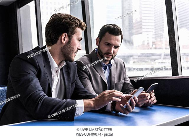 Two businessmen with cell phones talking on passenger deck of a ferry
