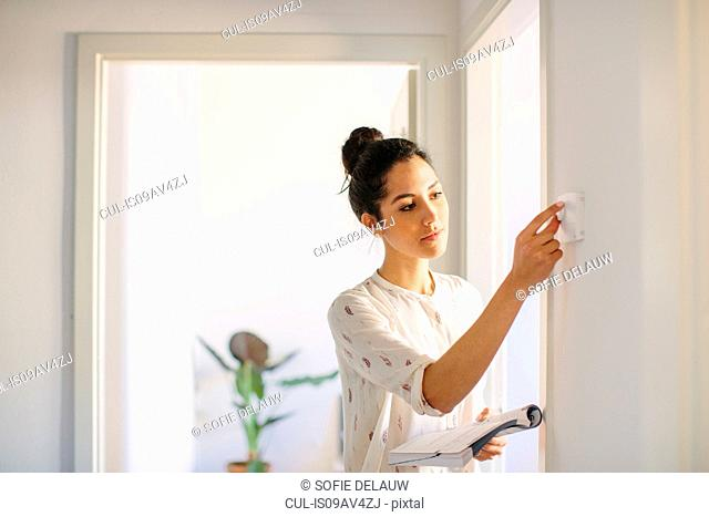 Young woman adjusting central heating control at home