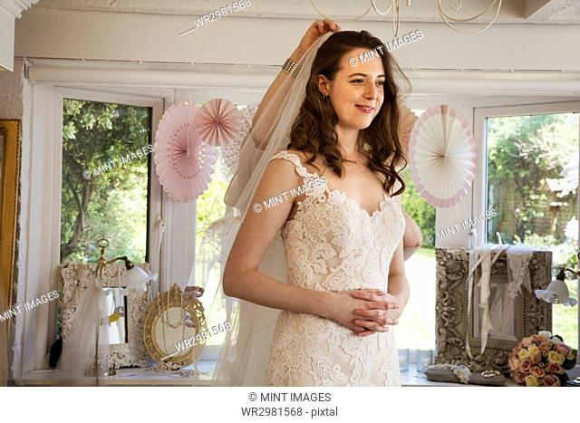 A bride to be, a young woman trying on wedding dresses in a specialist bridal boutique