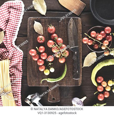 wooden cutting board with a knife and fresh red cherry tomatoes, beside a tied bundle of long raw spaghetti