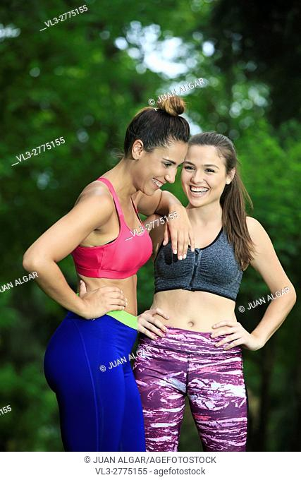 Portrait of two laughing sportswomen having fun in park after workout. Bokeh