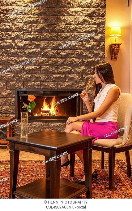 Business woman drinking champagne, sitting next to fireplace in hotel lobby