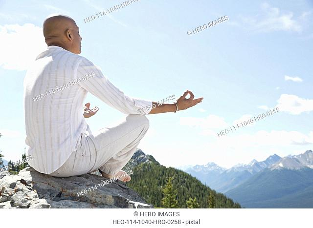 Mature man meditating on mountain top